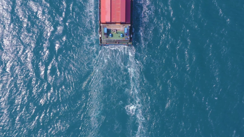 Top down Aerial View of a large container ship sailing at the sea for transporting shipments to other countries   | Shutterstock HD Video #1042694047