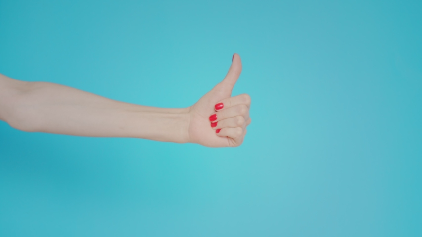 Woman's hand shows finger up, like or dislike, gesture on blue background. Copy space for advertisement. With place for text or image. Advertising area, mock up. Hand doubts the decision | Shutterstock HD Video #1042768237