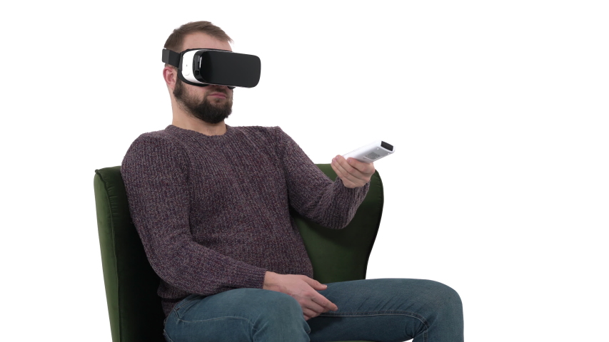 The man looks through the VR glasses and uses remote controller. Virtual reality. Futuristic technology concept | Shutterstock HD Video #1042778497