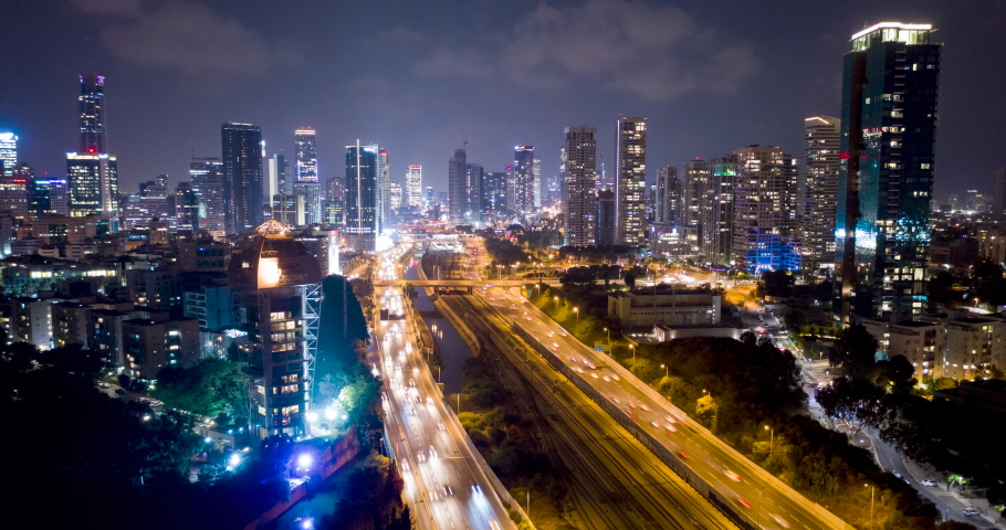 Night aerial hyperlapse of tel aviv skyline with urban skyscrapers, beautiful moving clouds, and cars on highway Israel | Shutterstock HD Video #1042781707