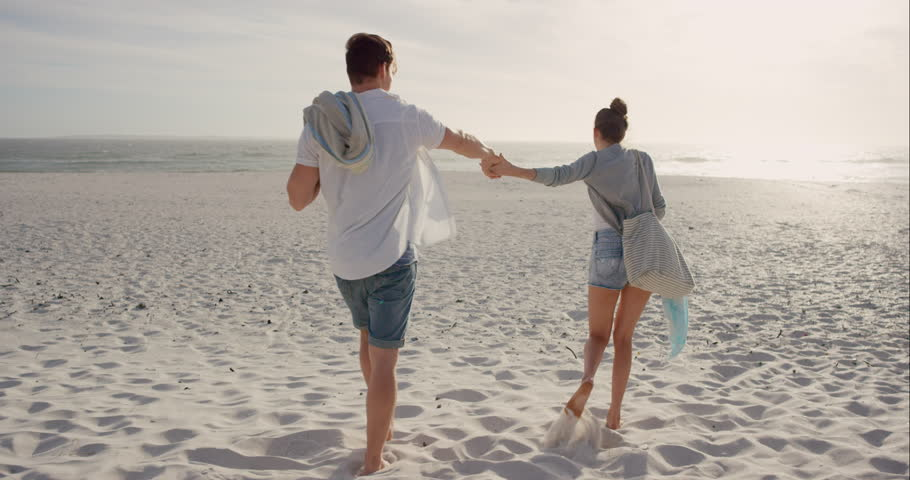 Young couple holding hands walking towards sunset on empty beach woman leading man on romantic vacation