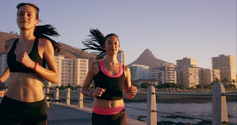 Two athletic woman running outdoors in slow motion on promenade at sunset near ocean enjoying evening run RED DRAGON