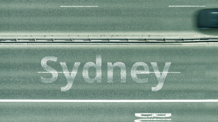 Aerial top down view of the road with cars revealing Sydney caption. Car travel in Australia conceptual clip | Shutterstock HD Video #1042793437