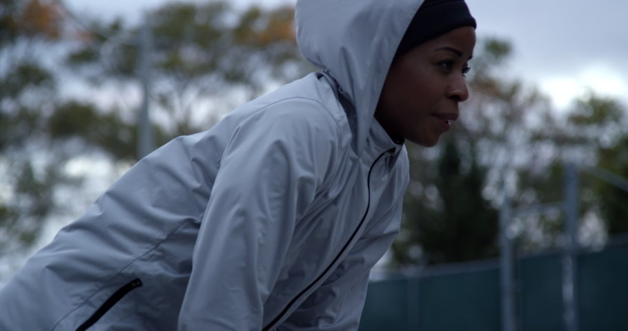 Runner in hooded running jacket leaning over after hard run breathing heavily, out of breath #1042803637