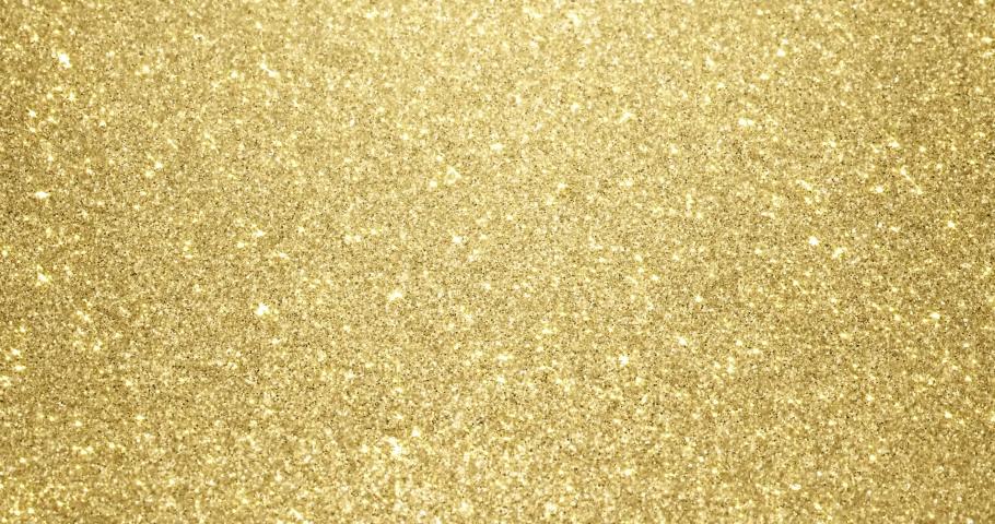 Gold glitter background with sparkling texture. Golden shimmering light, stars sequins sparks and glittering glow foil background | Shutterstock HD Video #1042924897