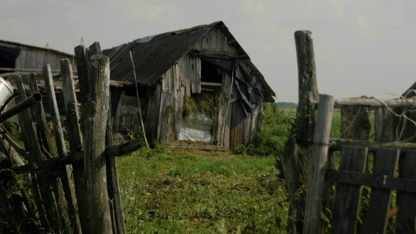 Old village house in summer in dilapidated condition - on the foreplan wooden gates | Shutterstock HD Video #1042970197