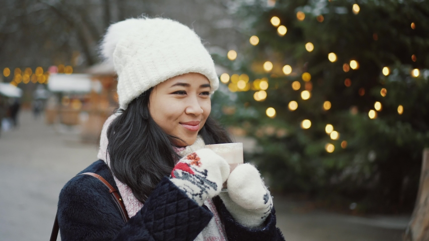 Pretty young woman drinks hot wine outside at Christmas market in Europe. Cute girl wears white hat and mittens in winter, drinking hot coffee or chocolate beside decorated with lights tree