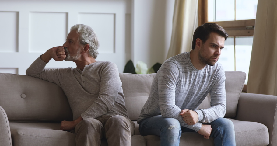 Angry frustrated stubborn senior old father and young adult grown son sit on sofa turn back ignore each other think of family conflict, two age generation gaps and problem in bad relationship concept | Shutterstock HD Video #1044003367
