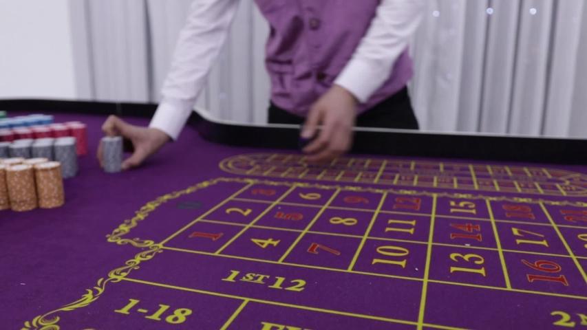 Dealer in casino moves chips on roulette table to winner | Shutterstock HD Video #1044311917
