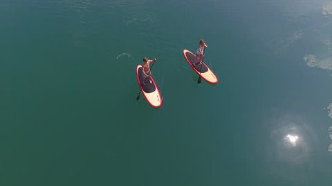 AERIAL: Surfer man and woman SUP boarding from lake island