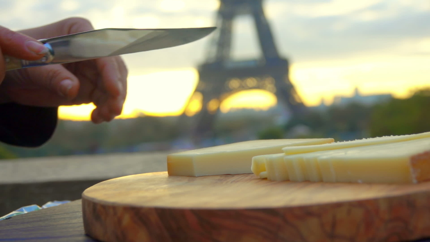Knife is slicing hard goat cheese on a wooden board on the backdrop of the Eiffel Tower, Paris, France | Shutterstock HD Video #1044717457