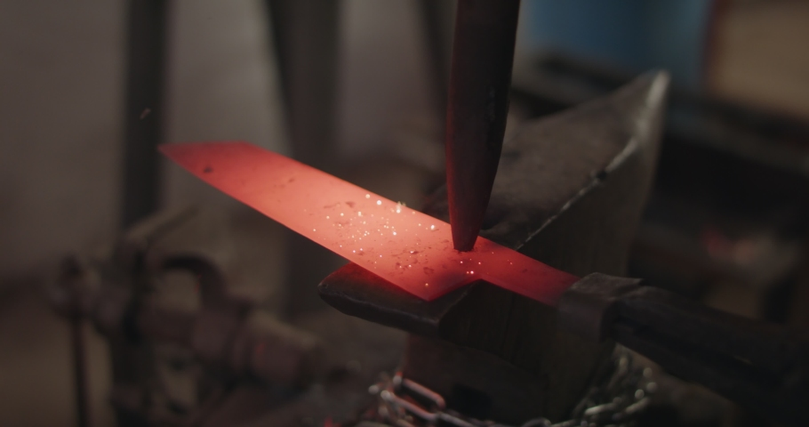 Blacksmith finalizing forging of knife by hammer and chisel engraving. Slow motion, extreme close up, macro detail. | Shutterstock HD Video #1044735757