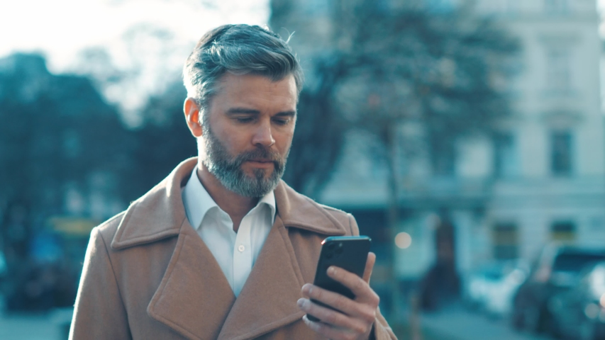 Caucasian middle aged business man walks along the street looks around and uses phone texting message works feels happy slow motion outdoor business tehnology close up slow motion   Shutterstock HD Video #1044823627