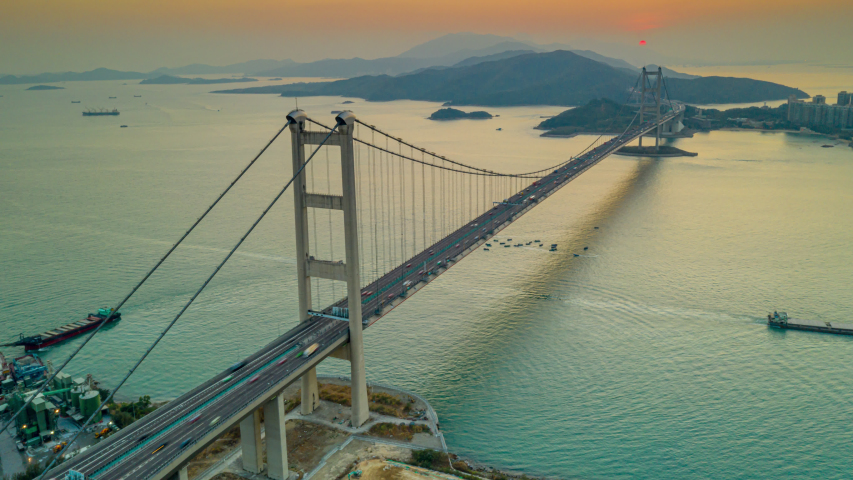 Hyperlapse or Dronelapse Aerial view of Traffic of car at Tsing ma bridge in Tsing yi area of Hong Kong at sunset. Day to night   Shutterstock HD Video #1044848287