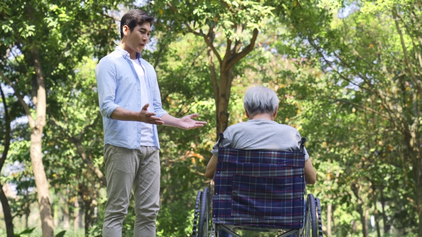 Young asian adult son talking to wheelchair bound demoralized senior father outdoors in a park   Shutterstock HD Video #1044871687