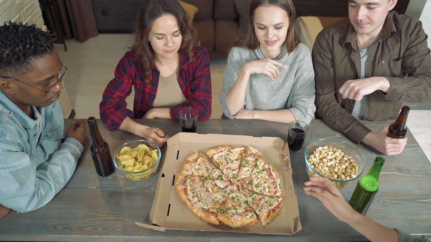 Happy multiethnic friends drinking beer, eating pizza and having fun together in the living room at home | Shutterstock HD Video #1044995197