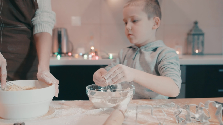 Mother and son baking Christmas cookies in the kitchen. Family life before the holidays at home. | Shutterstock HD Video #1045004137