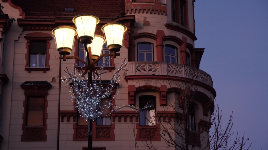 City holiday landscape at dusk. The facade of the building with beautiful architecture. Vintage street lamp decorated with Christmas shining garland. Great place for vacation or pleasant evening walk | Shutterstock HD Video #1045012417
