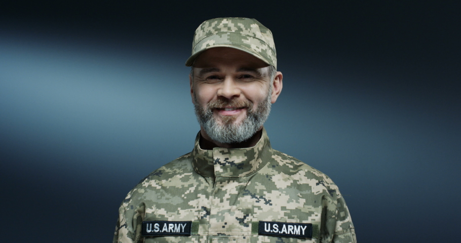 Portrait shot of the handsome strong and brave Caucasian soldier of USA forces smiling joyfully to the camera. Close up. | Shutterstock HD Video #1045021657