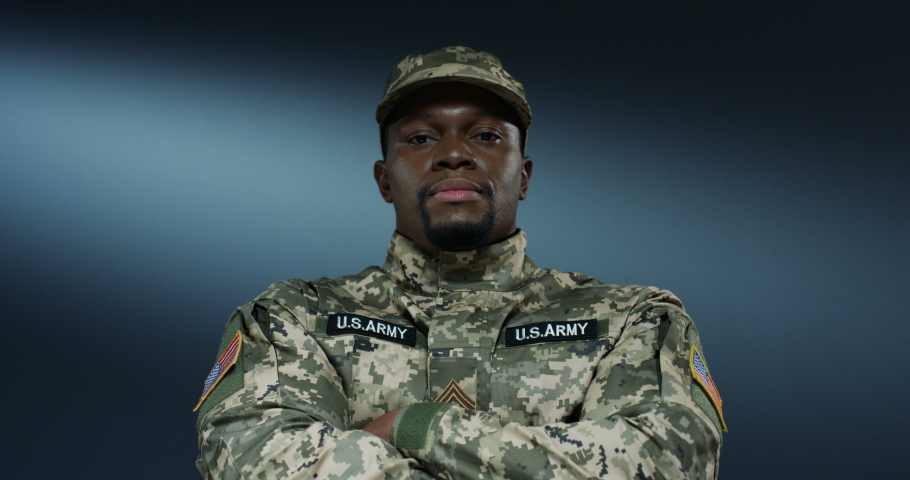 Potrait shot of the handsome and strong African American man US soldier looking straight at the camera and crossing hands in front of him. | Shutterstock HD Video #1045021717
