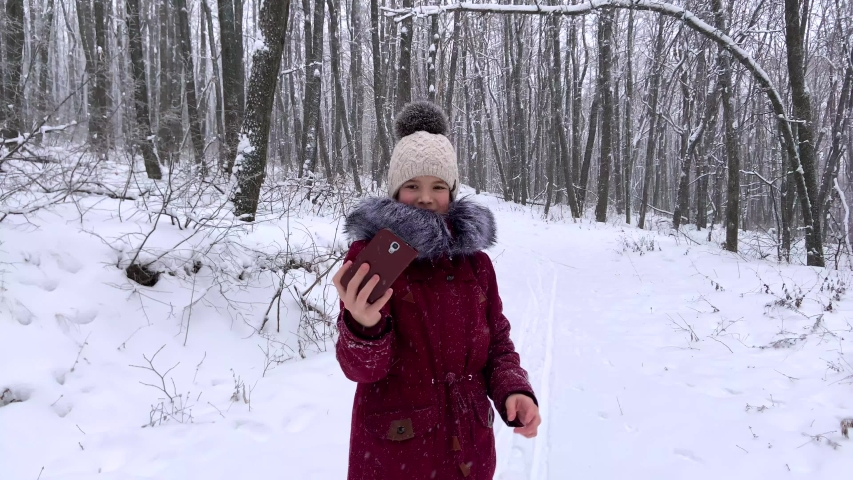 Teenager young caucasian girl taking selfie photos on smartphone and posing for a photo in the Russian winter snowy forest. Healthy open air spending holidays or weekend outdoors in cold weather. | Shutterstock HD Video #1045033387