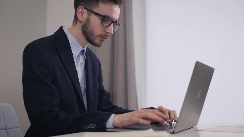 Side view portrait of handsome Caucasian businessman in eyeglasses typing on laptop. Young intelligent man in elegant suit working online. Lifestyle, working, intelligence. | Shutterstock HD Video #1045058227