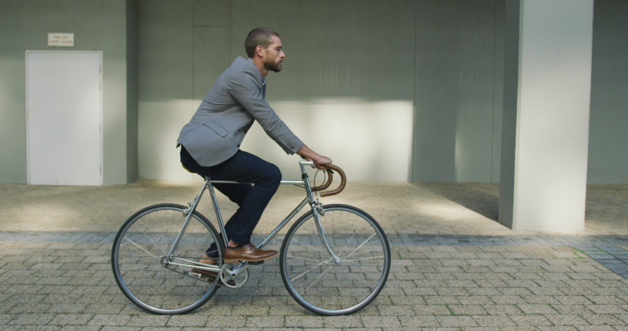 Side view of a young Caucasian businessman on the go in the city, riding a bike in the street, slow motion | Shutterstock HD Video #1045109647