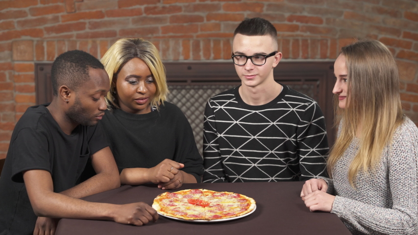 Multi-racial friendship concept. Friends are sitting in stylish interior café and eating tasty hot pizza | Shutterstock HD Video #1045159777