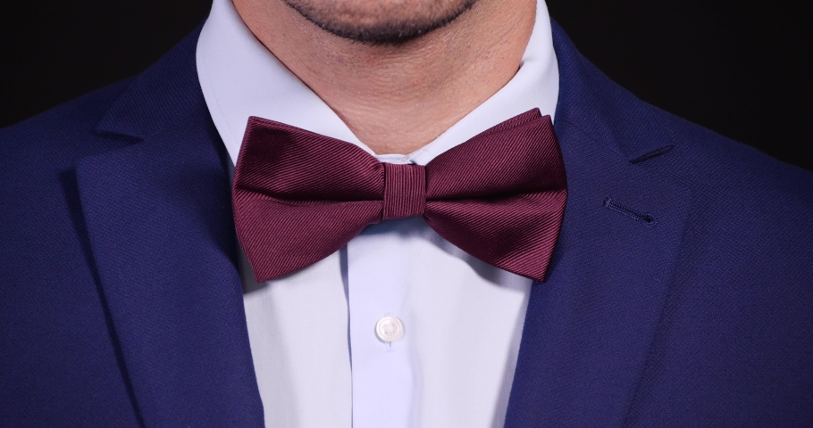 Man in elegant suit adjusting bow tie on black background, closeup | Shutterstock HD Video #1045239397