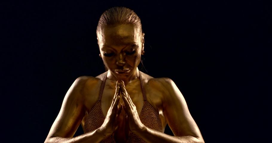 Close-up of the body, biceps toned athletic girl bodybuilder in a top, she is in the Studio on a black background, her skin has a Golden pigment. She puts her hands on Namaste. | Shutterstock HD Video #1045281427