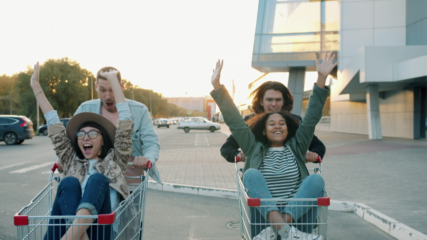 Men and women joyful friends are riding shopping carts in car park in city having fun laughing together. Friendship, freedom and entertainment concept. | Shutterstock HD Video #1045402147