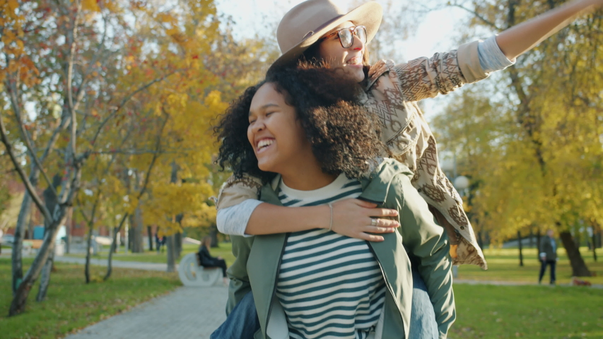 Portrait of beautiful mixed race lady giving piggyback ride to happy female friend laughing walking in city park together. Lifestyle, fun and friendship concept. | Shutterstock HD Video #1045402177