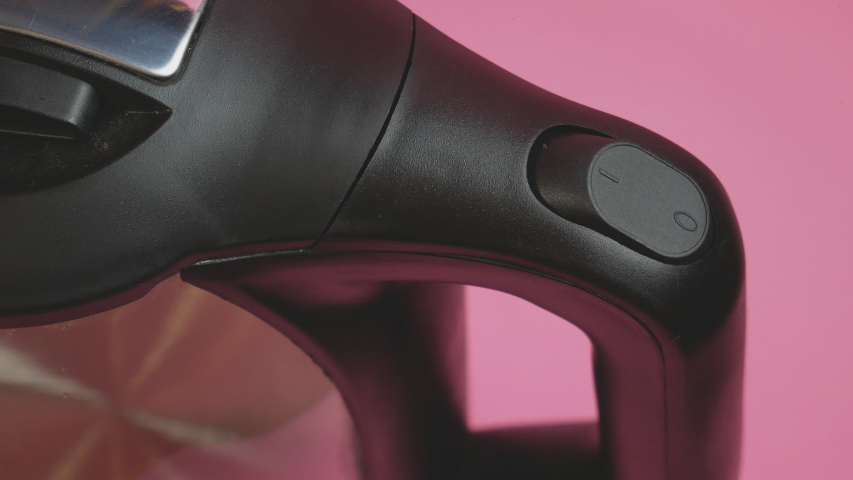 Hand reaches to turn on the switch of an electric kettle on a pink background   Shutterstock HD Video #1045425097