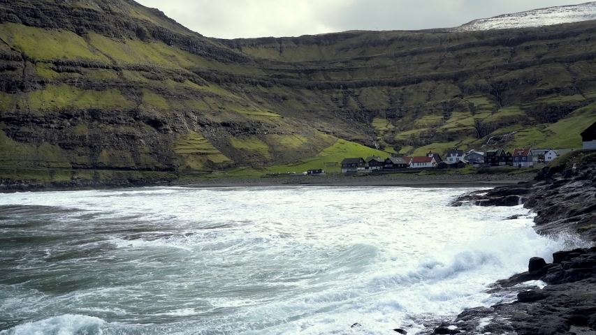 Dramatic scene of pittoresque scandinavian village located in Faroe Islands. Remote settlement surrounded with snow covered mountains and deep narrow fjords in Faroe Islands. | Shutterstock HD Video #1045431577