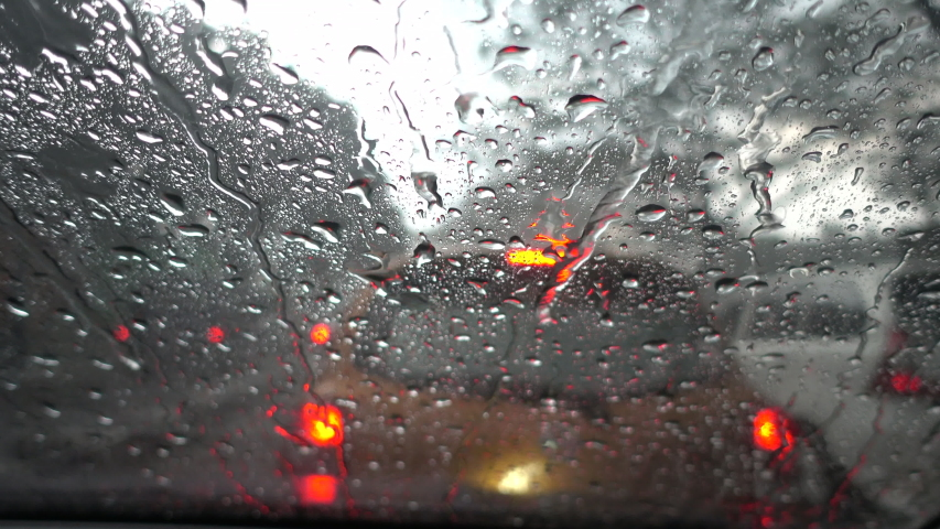 Rain falling on car windshield view. Drive car on traffic jam street at heavy rain storm, inside a car driving,blurred traffic light background. | Shutterstock HD Video #1045577917