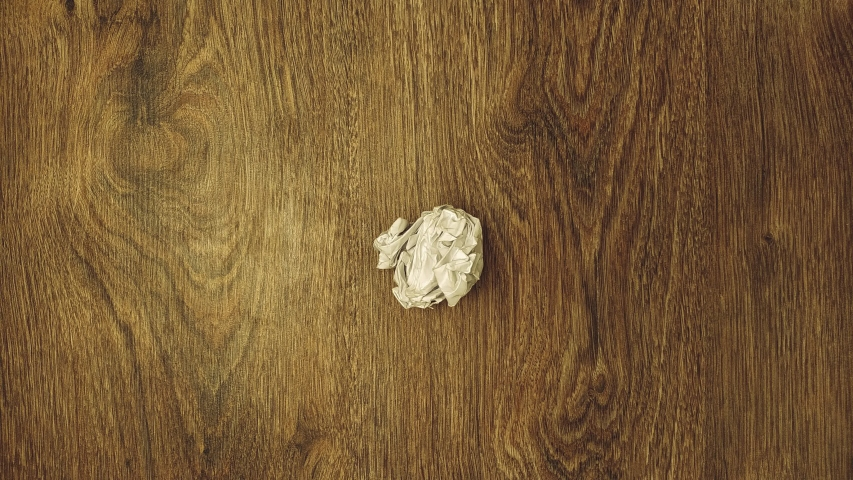 Stop motion. White paper wrinkles and unfolds on a wooden background. | Shutterstock HD Video #1046152867