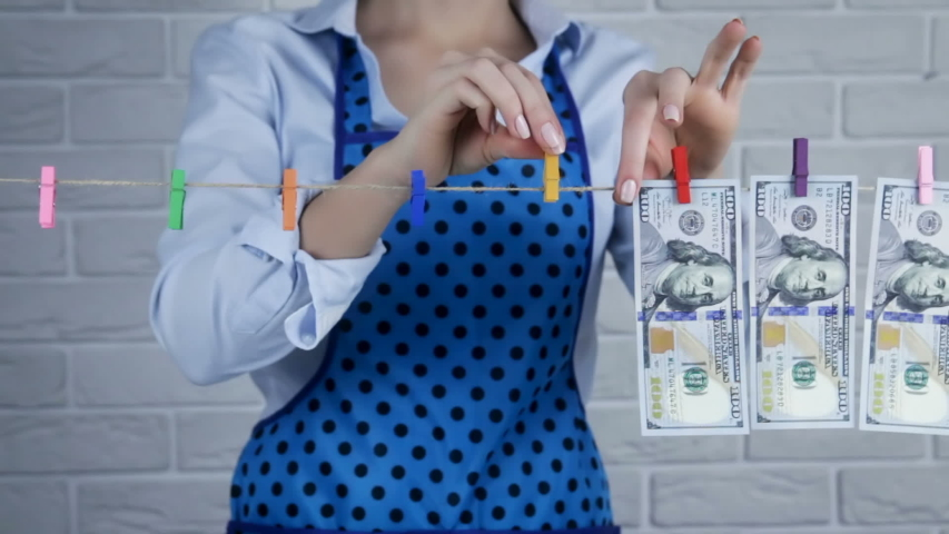 Woman is laundering money. The concept of money laundering. Financial fraud. Love of money. A financial crime. Legalization of criminal proceeds. | Shutterstock HD Video #1046181667