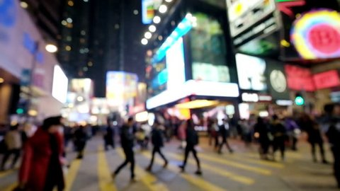Slow motion video of people moving at crossroad in crowded evening city street. Hong Kong. Blur effect