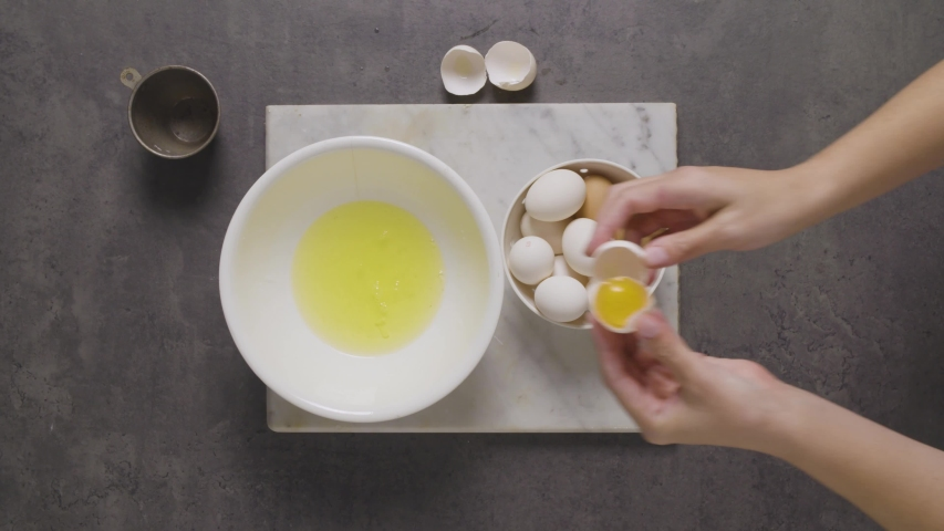 Cracking eggs into a bowl and separating the white | Shutterstock HD Video #1046441257