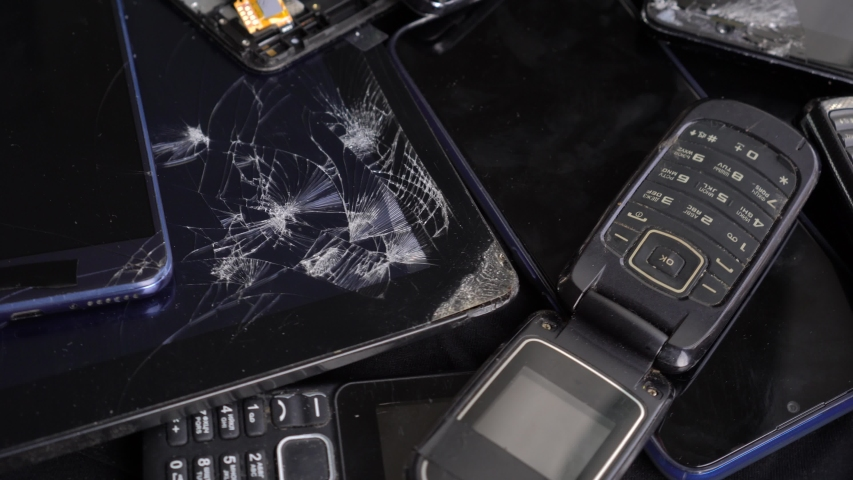 Obsolete old cell phones and broken smartphones with cracked screen. Used digital tablets and smart watch. Recycle  e-waste | Shutterstock HD Video #1046613607