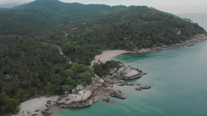 Aerial view of scenery beach. Travel to wild jungles of Thailand. Sea waves leak white sand. Palm trees pass below the drone   Shutterstock HD Video #1046694007