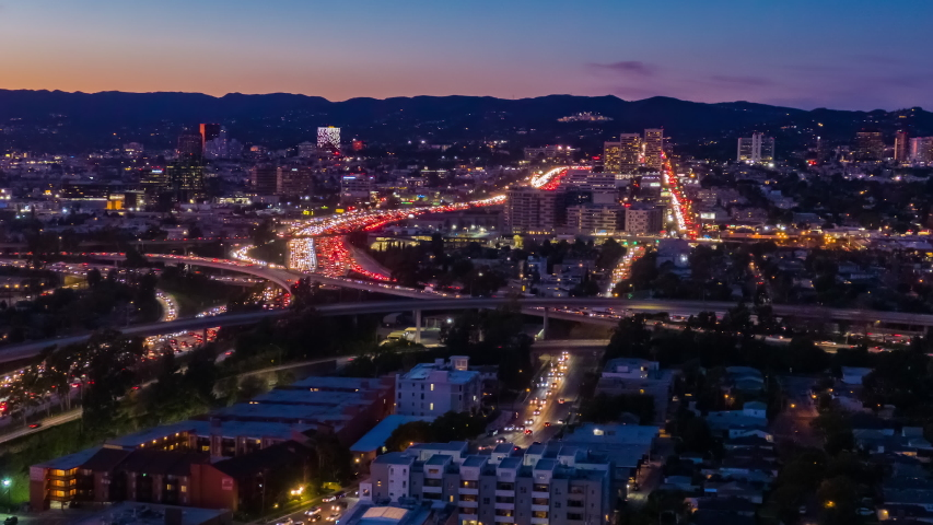 Aerial view of freeway and interstate road traffic during rush hour on the I-405 and I-10 in urban Los Angeles California with cars and car lights below at night.   Shutterstock HD Video #1046799487