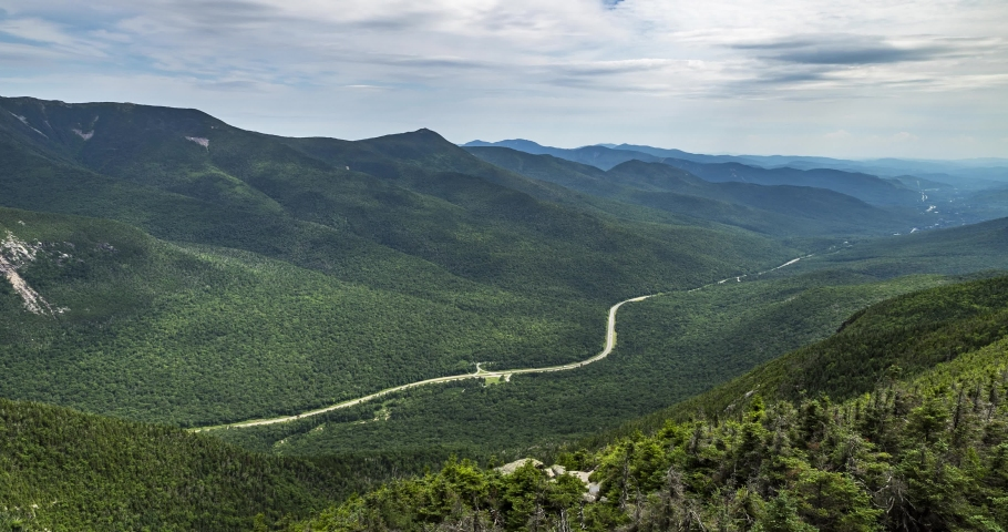 Time lapse from the top of Canon Mountain mid day in New Hampshire USA. Clouds flying overhead with view of the highway far below. Includes 2 versions, one tilting up and 1 stationary.   Shutterstock HD Video #1046823067