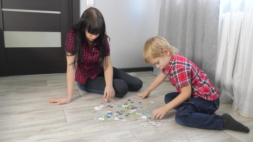 Happy family collection puzzles teamwork. development of fine motor skills and thinking. little boy a and girl mom lifestyle collect mosaic puzzles. | Shutterstock HD Video #1046885677