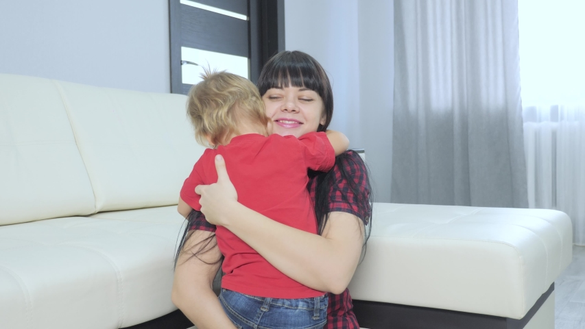 Happy family little daughter hugs mom indoors. lifestyle little girl hugs woman in remembrance joy happiness a happy family | Shutterstock HD Video #1046890867