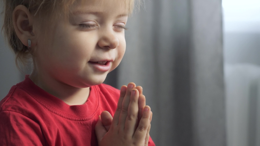 Little daughter girl makes a wish prays bedtime religion concept. prayer child indoors praying by bed in front lifestyle of window | Shutterstock HD Video #1046890897