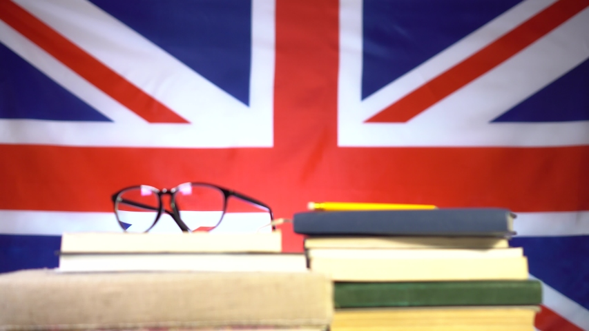 Cute guy student with glasses is looking for information in a book from a pile of books on the background of the flag of Great Britain. Education in the UK. Education concept. | Shutterstock HD Video #1046908897