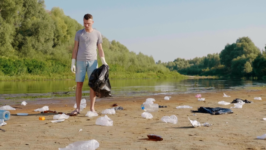 Man is collects plastic trash on the banks of dry and polluted river or lake and listens favorite song, singing along. Ecological catastrophy. Anthropogenic influence. 4K slowmotion footage. | Shutterstock HD Video #1046929537