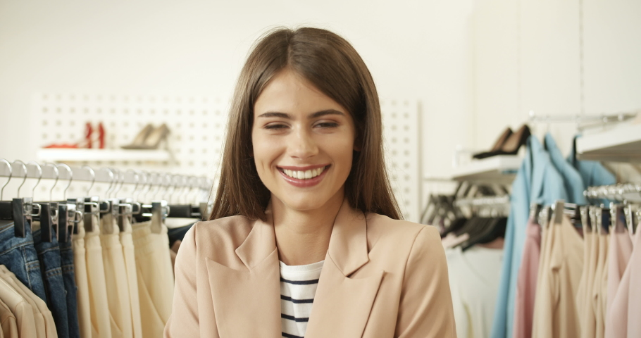 Close up of cheerful happy young Caucasian charming woman smiling joyfully to camera in clothing store. Pretty girl laughing at shopping in shop of fancy clothes. Portrait of female fashion buyer. | Shutterstock HD Video #1046966227