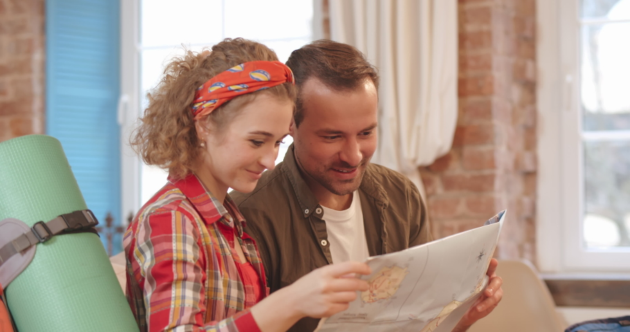 Excited young couple planning their holiday holding map and pointing to travel destination sitting on couch at home. | Shutterstock HD Video #1046968897